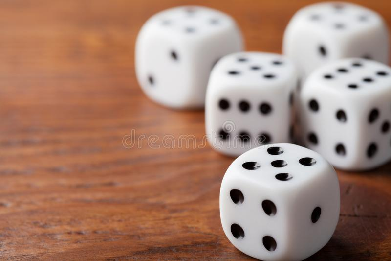 Dice on rustic wooden table. Gambling devices. Game of chance concept. Macro shot. stock image