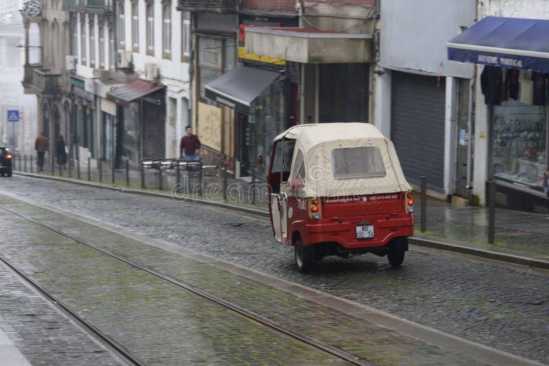 8 dicembre 2019, Porto, Portogallo Autovettura rossa su una tipica strada della città con la nebbia immagine stock