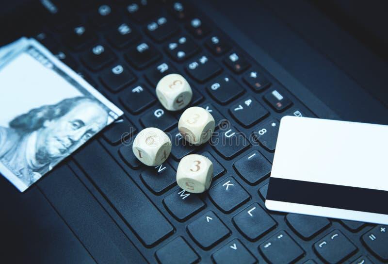 Dices 100 доллар и кредитных карточек на клавиатуре компьтер-книжки играть в азартные игры он-лайн стоковое фото rf