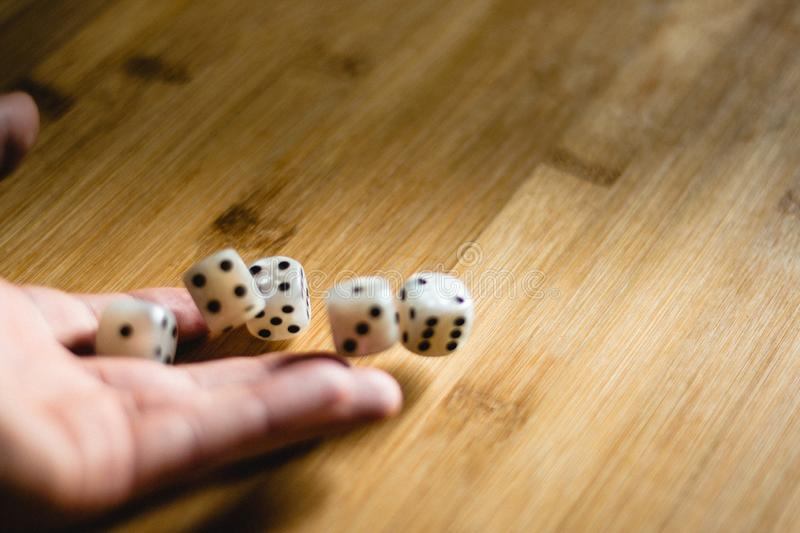 Dices bouncing on a wooden table. Single or group stock image