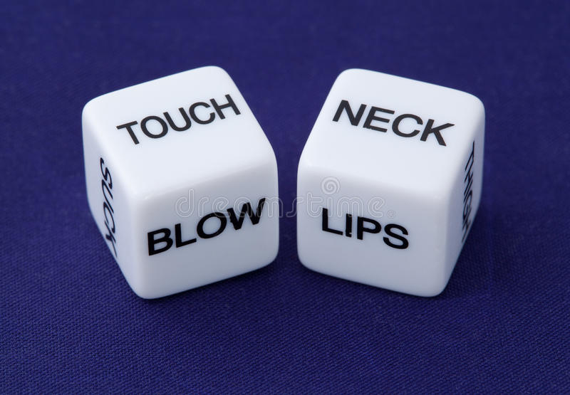 Dices with erotic messages. White dice with erotic messages TOUCH, BLOW, LIPS, NECK on the sides on blue background royalty free stock images