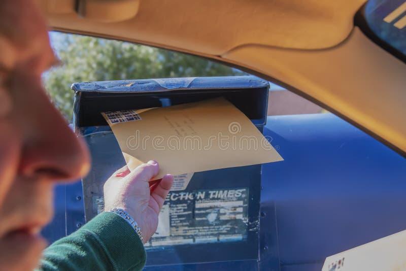 Dichiarazione dei redditi della spedizione dell'uomo - grande busta ad azionamento dalla cassetta delle lettere con il fronte vag fotografia stock libera da diritti