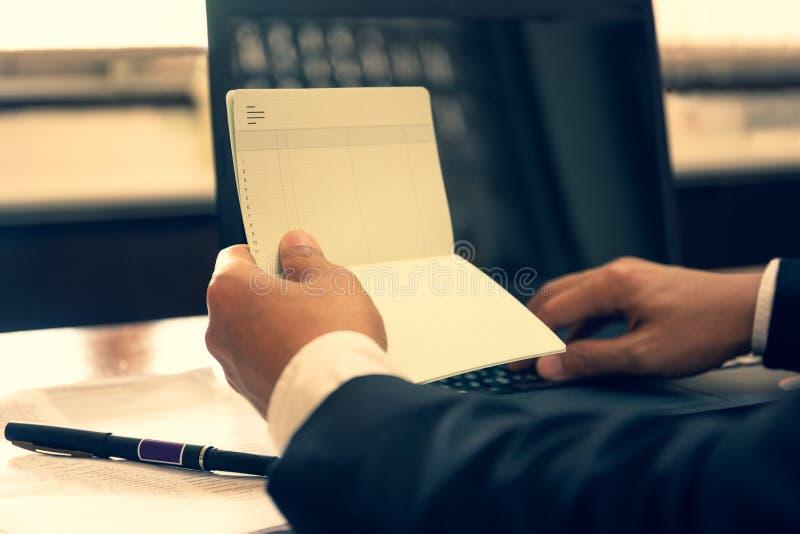 Dichiarazione e lavoro finanziari del libro della tenuta della mano di affari con il computer portatile immagini stock libere da diritti