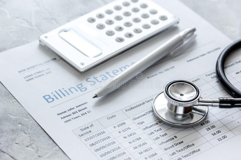 Dichiarazione treatmant medica di fatturazione con lo stetoscopio ed il calcolatore su fondo di pietra immagine stock libera da diritti