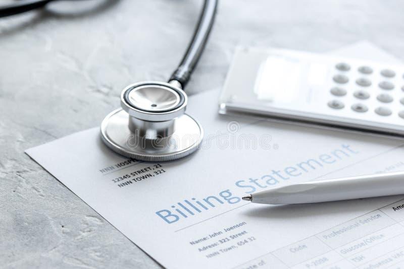 Dichiarazione treatmant medica di fatturazione con lo stetoscopio ed il calcolatore su fondo di pietra fotografia stock