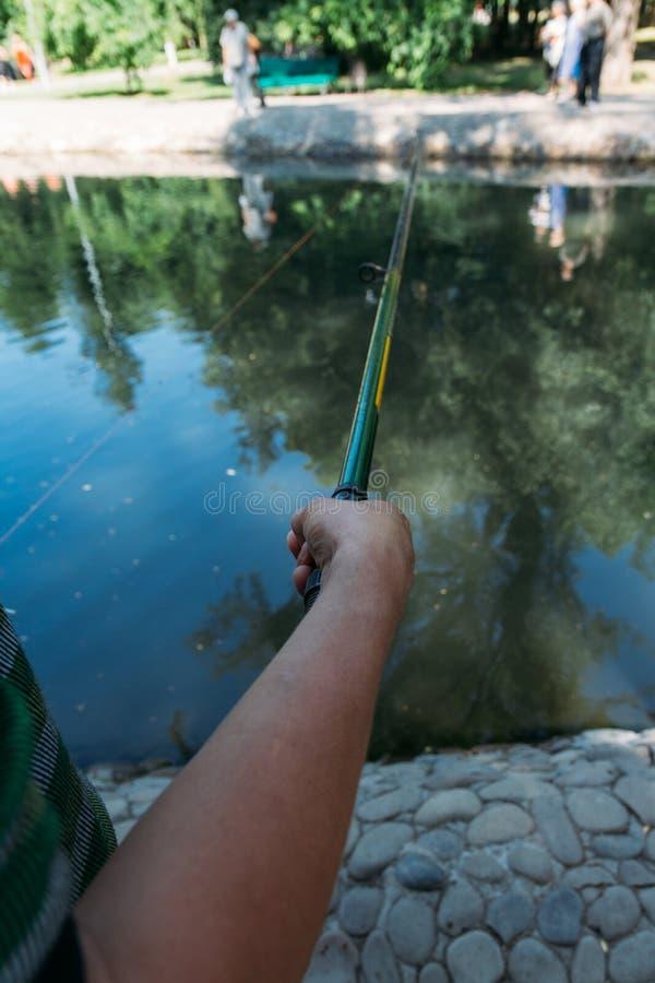 Dicht-geschoten van menselijke handen die een hengel op de voorgrond houden een mens houdt een hengel over het water, vangt visse royalty-vrije stock afbeeldingen