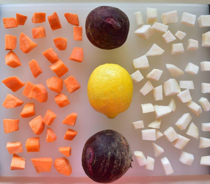 Dicht omhoog geïsoleerd van gehakte wortelgewassen klaar voor oven het roosteren met citroen royalty-vrije stock afbeeldingen