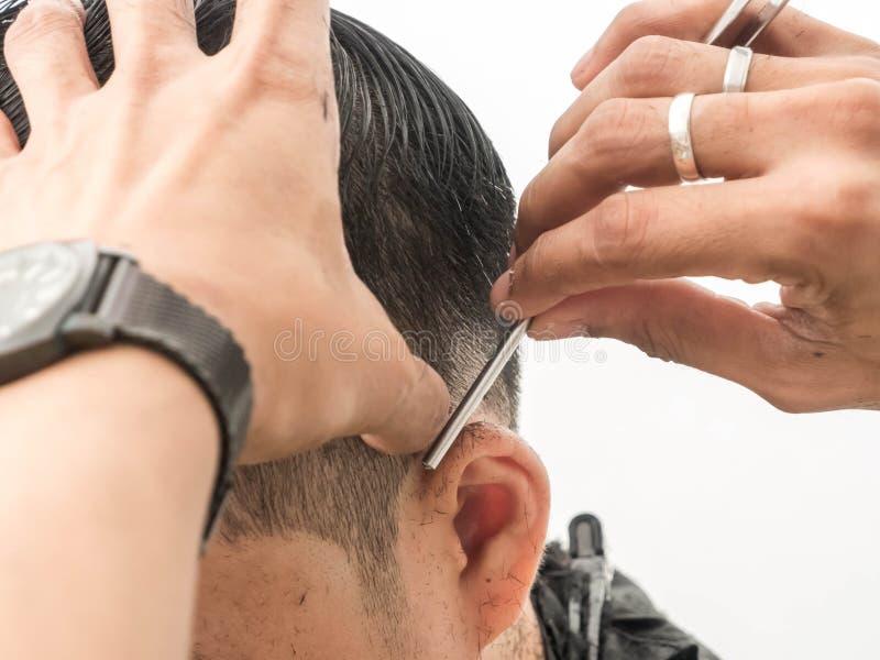 Dicht omhoog makend modieus kapsel bij salon kapper die hem scheren met scheermes Schoonheid, moderne stijl, levensstijl, tendens stock foto's