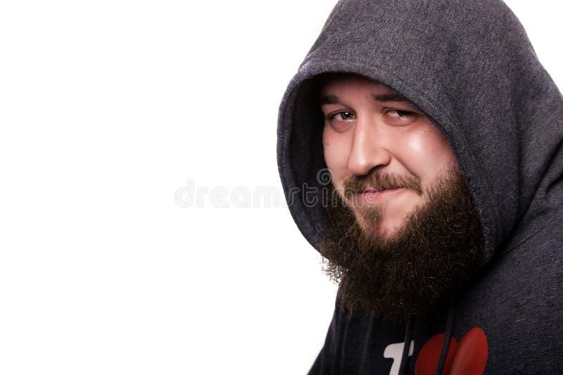 Dicht portret van een kerel met een baard en snor in kapyushone stock afbeelding