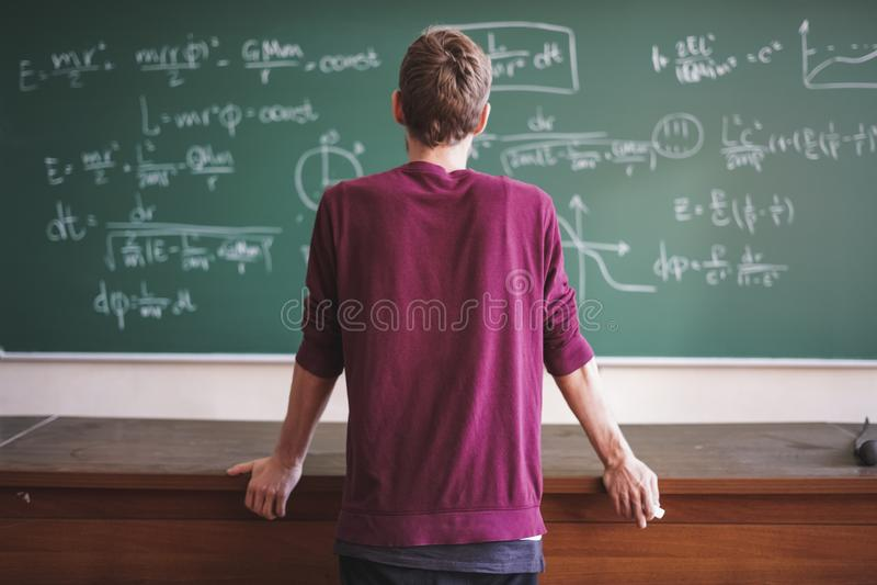 Dicht portret van jonge gebaarde professorsleraar in toevallig met bord met erachter formules stock foto's