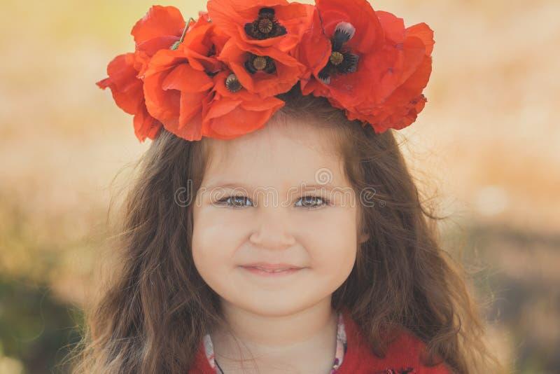 Dicht portret van weinig kindmeisje met grote wangen bruine ogen en steenbolklippen die modieuze rode kleding met de papaver o dr royalty-vrije stock fotografie