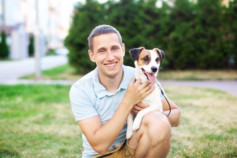 Dicht verband tussen de hond en zijn eigenaar De gelukkige eigenaar loopt met een aanbiddelijke hond en een knuffel van Jack Russ stock afbeeldingen