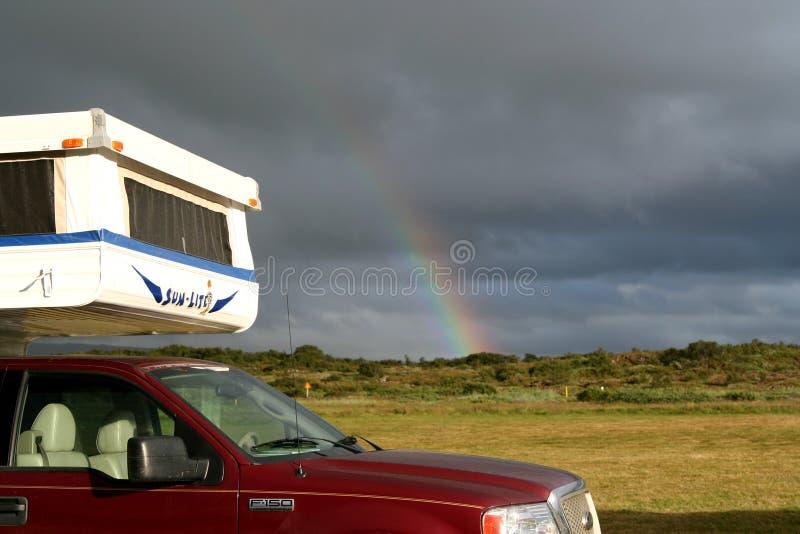 DICHTBIJ REYKJAVIK, IJSLAND - JULI 28 2008: Regenboog over kap van een Kampeerauto stock afbeelding