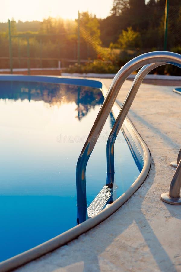 Dichte mening van modern zwembad bij zonsondergang bij hotel Zonlicht aan oppervlakte De de zomervakantie, vakantie, ontspant, de stock foto