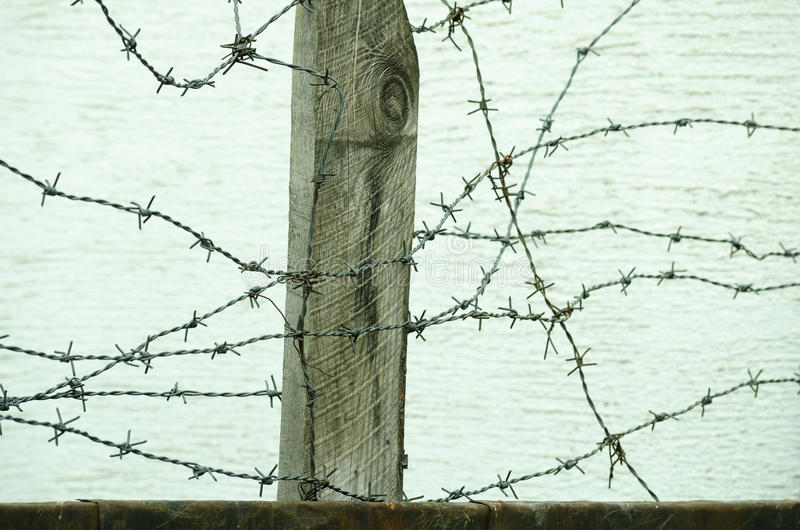 Dichte omhooggaand van de prikkeldraadomheining in de oorlogsstreek om gevangenen tegen het ontsnappen van aan kamp te beschermen stock afbeelding