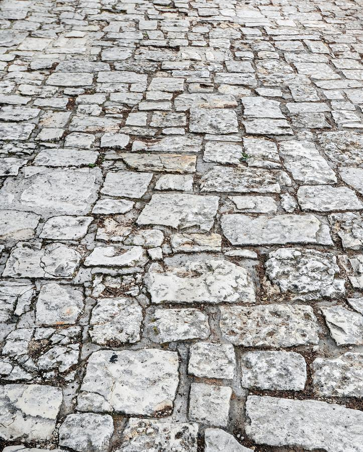 Dichte omhooggaand van de steenweg Oude bestrating van graniet Grijze keistoep Spot omhoog of uitstekende grungetextuur stock foto's