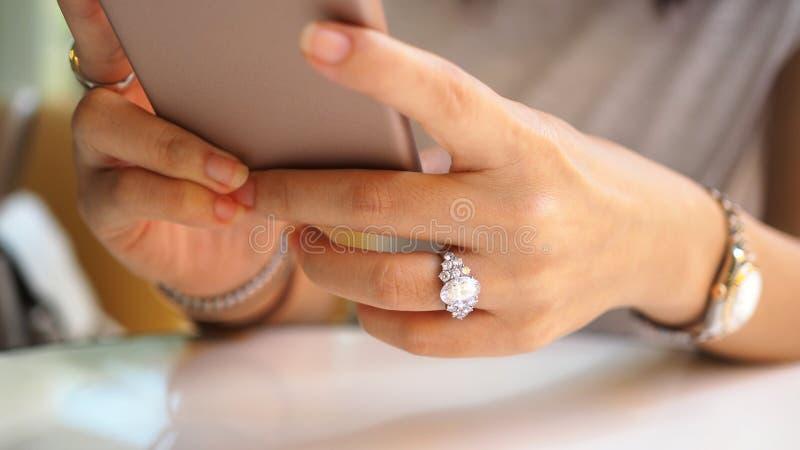 Dichte omhooggaand van de vrouwenhand op diamantring die een mobiele telefoon met behulp van stock afbeeldingen