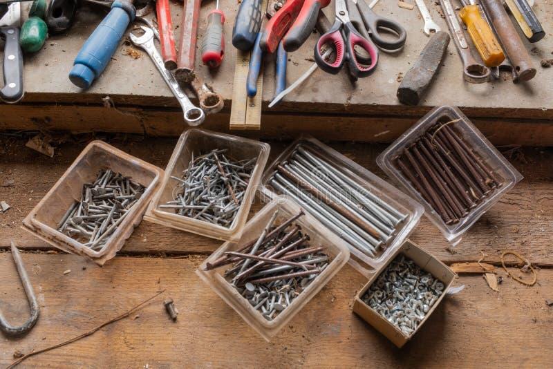 Dichte omhooggaand van een assortiment van spijkers, schroeven en hulpmiddelen op een houten het werkbank, natuurlijk licht stock fotografie