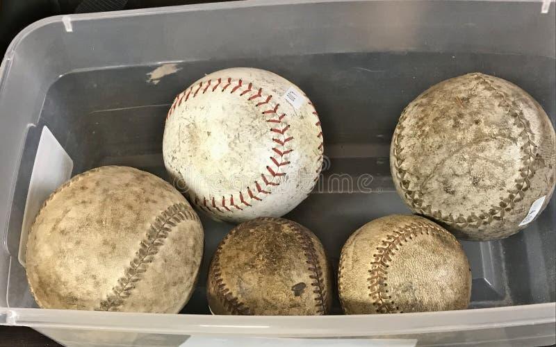 Dichte omhooggaand van gebruikte twee baseballs en drie gebruikte softballs in een plastic bak stock fotografie