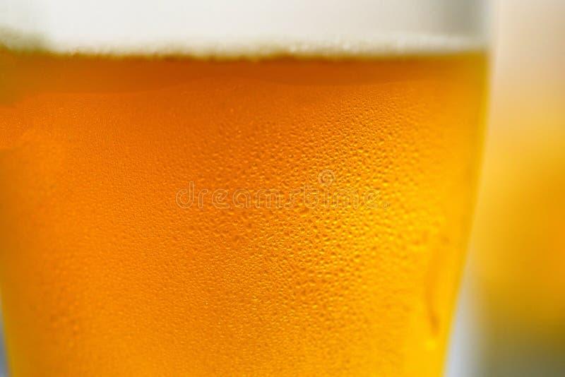 Dichte omhooggaand van het bierglas van de mok van het bellenbier met waterdaling stock afbeeldingen