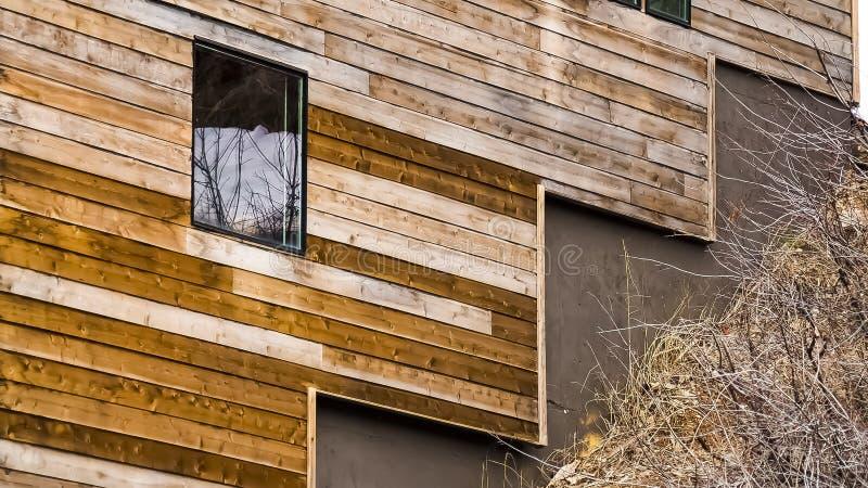 Dichte omhooggaand van het panoramakader van huis buiten met bruine horizontale raad op de muur stock afbeeldingen