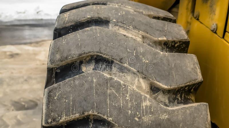 Dichte omhooggaand van het panoramakader van zwart rubberwiel met diagonaal loopvlak van een bouwvoertuig stock foto