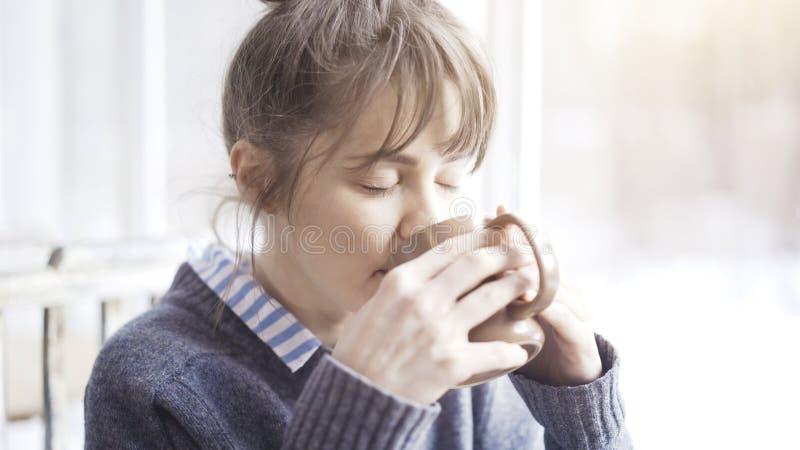 Dichte omhooggaand van het witte vrouwelijke drinken houdend een kop thee bekijkt de camera royalty-vrije stock foto