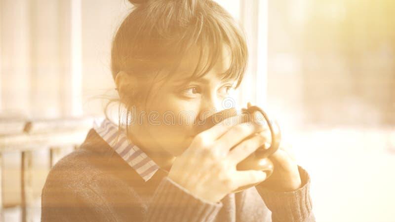 Dichte omhooggaand van het witte vrouwelijke drinken houdend een kop thee bekijkt het venster stock fotografie