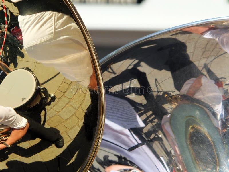 Dichte omhooggaand van musici van een fanfarekorps dat in hun instrumenten wordt weerspiegeld die bij de openbare wedstrijd van m royalty-vrije stock fotografie