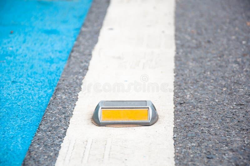 Dichte omhooggaand van reflector of nagel op asfaltweg stock fotografie
