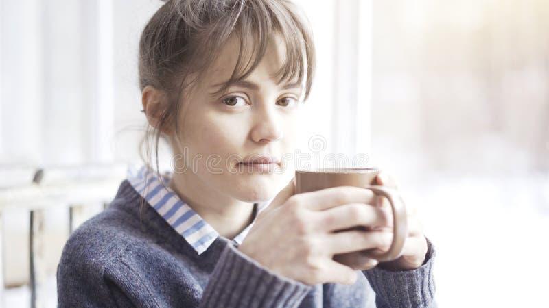 Dichte omhooggaand van wit wijfje die een kop thee houden bekijkt de camera royalty-vrije stock afbeeldingen