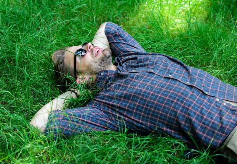Dichter aan aard De aard vult hem met versheid en inspiratie Legt de mensen ongeschoren kerel op groene grasweide Mens stock afbeeldingen