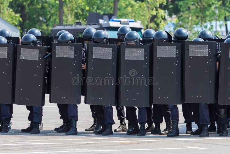 Dichtes System der Polizei mit Metallgepanzerten Brettern vor Soldaten Polizeibeamten halten ein System in den Sturzhelmen, schwe lizenzfreie stockbilder