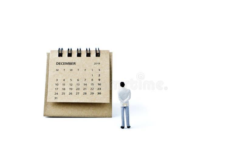 diciembre Haga calendarios la hoja y al hombre plástico miniatura en la parte posterior del blanco imagen de archivo libre de regalías