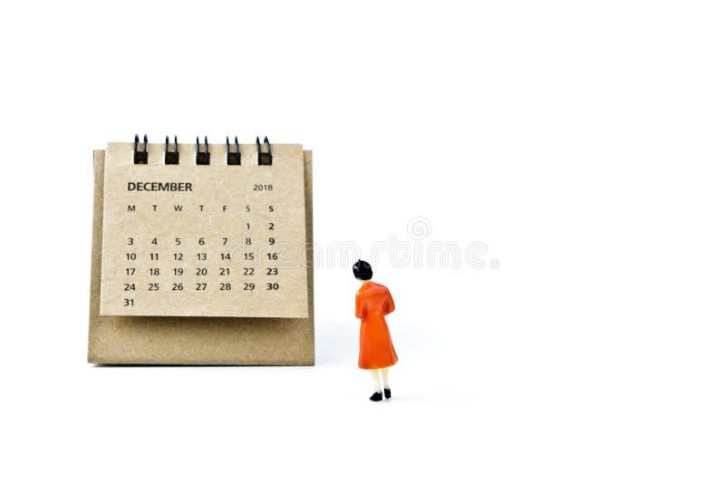 diciembre Haga calendarios la hoja y a la mujer plástica miniatura en los vagos blancos foto de archivo libre de regalías