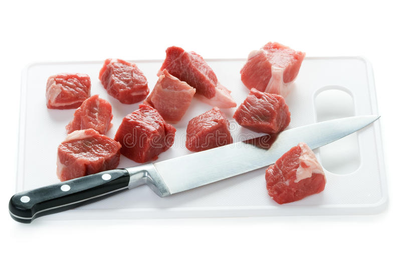 Dicing raw lamb with a kitchen knife. Raw lamb diced with kitchen knife and chopping board stock image