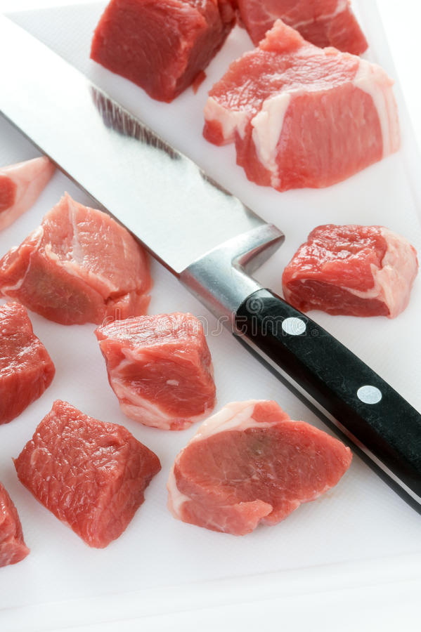 Dicing raw lamb with a kitchen knife. Raw lamb diced with kitchen knife and chopping board royalty free stock photo