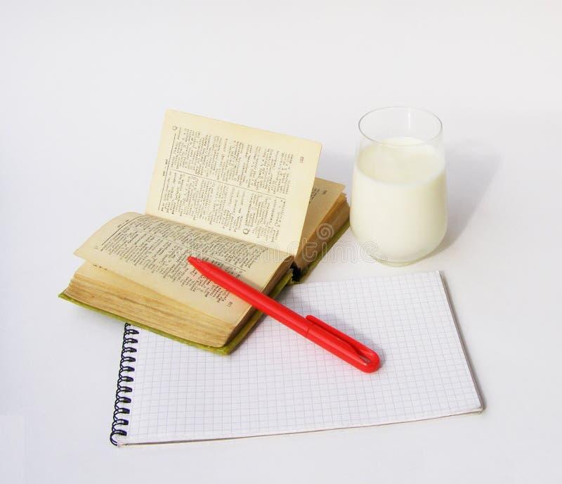 Dicionário e vidro do leite fotos de stock