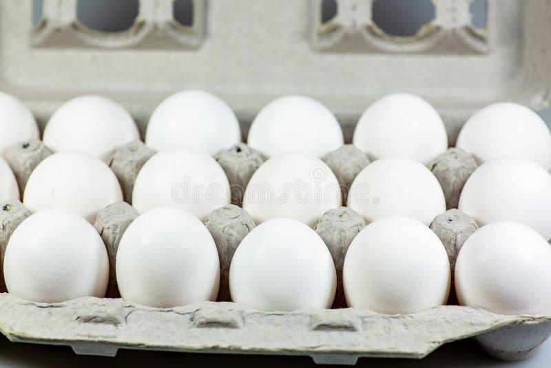 Diciotto uova in loro cassa del cartone che aspetta per essere usato dal cuoco fotografie stock