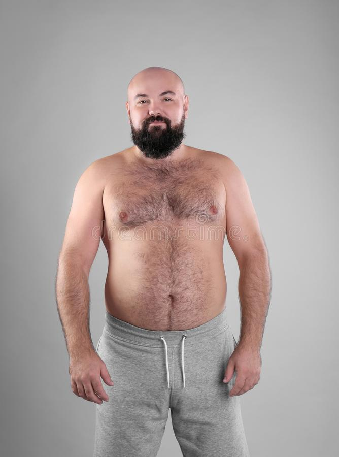 Dicker Mann auf grauem Hintergrund lizenzfreies stockbild