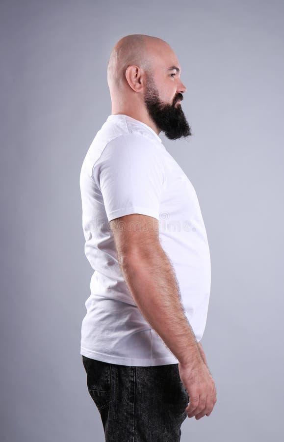 Dicker Mann auf grauem Hintergrund stockbild