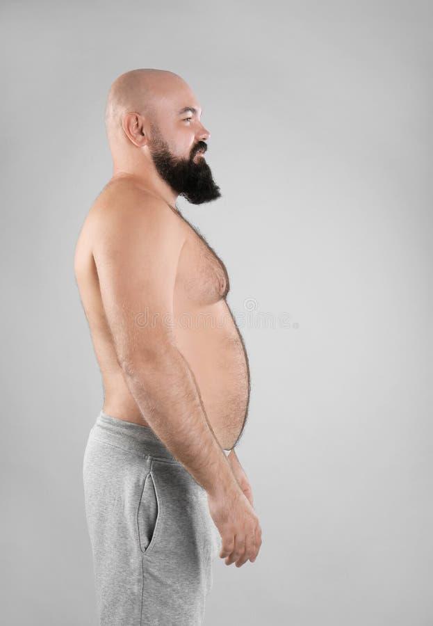 Dicker Mann auf grauem Hintergrund stockbilder
