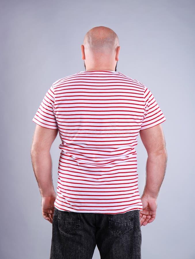 Dicker Mann auf grauem Hintergrund lizenzfreie stockbilder