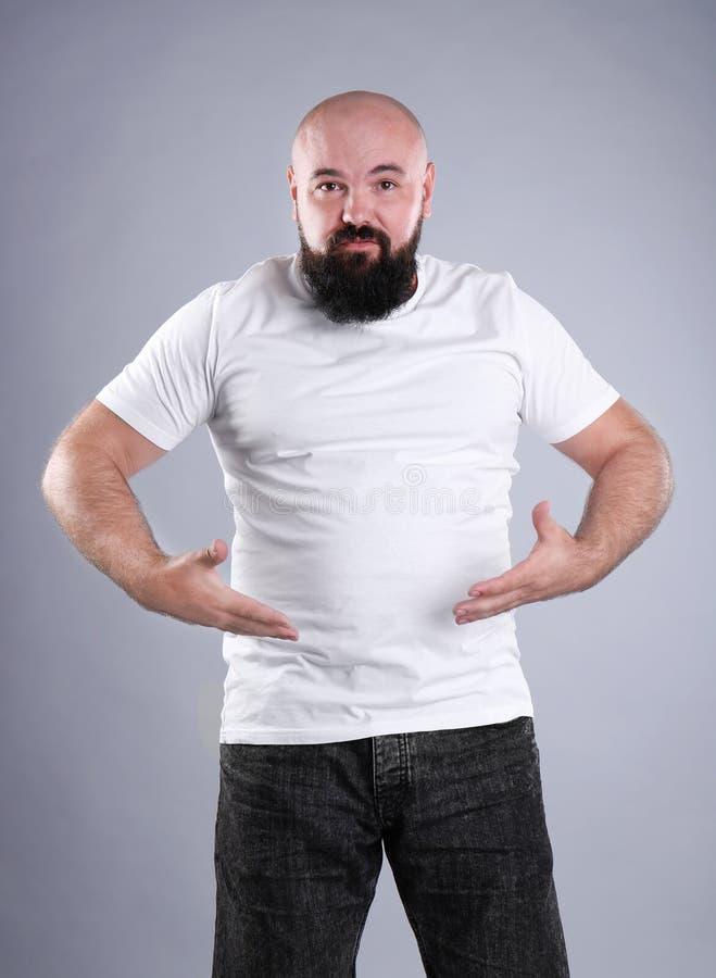 Dicker Mann auf grauem Hintergrund lizenzfreie stockfotos