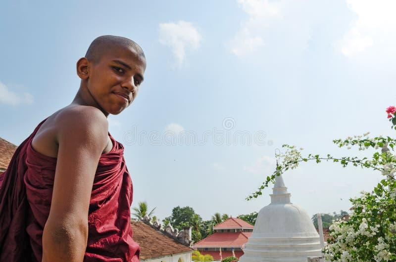 Dickwella Sri Lanka, 04-15-2017: Den unga buddistiska munken på bakgrunden av en buddistisk pagod ser kameran royaltyfria bilder