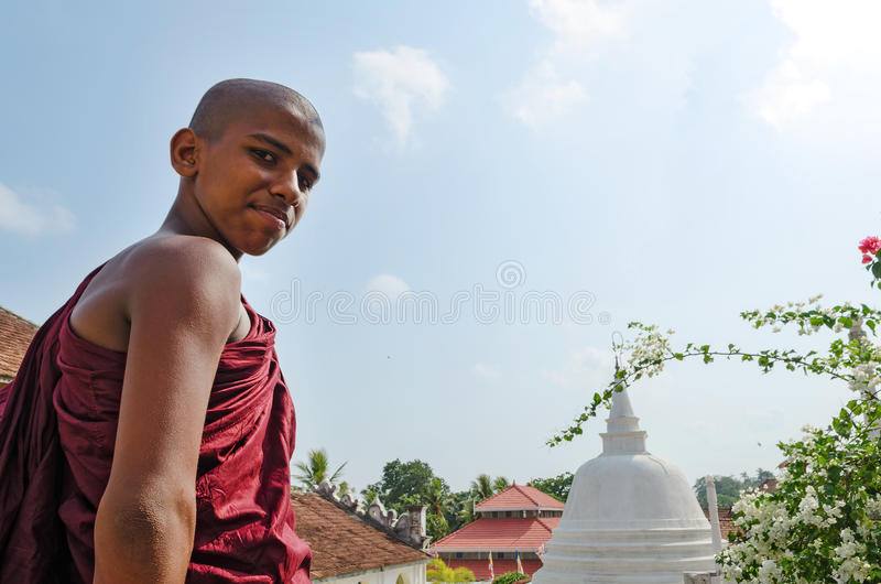 Dickwella, Sri Lanka, 04-15-2017: Il giovane monaco buddista sui precedenti di una pagoda buddista esamina la macchina fotografic immagini stock libere da diritti