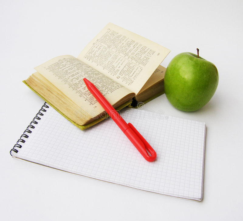 Dictionary. Notebook, the dictionary, the red pen and green apple on a white background stock photo