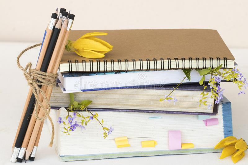 Dictionary ,book for study of student. Dictionary ,book ,notebook for study of student and pencil bundle by rope with flower decoration on table royalty free stock photography