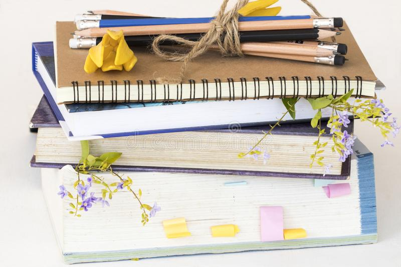 Dictionary ,book for study of student. Dictionary ,book ,notebook for study of student and pencil bundle by rope with flower decoration on table royalty free stock image