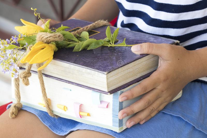 Dictionary ,book for study of student. Student girl children holding Dictionary ,book ,notebook bundle by rope for study with flower decoration on table royalty free stock images